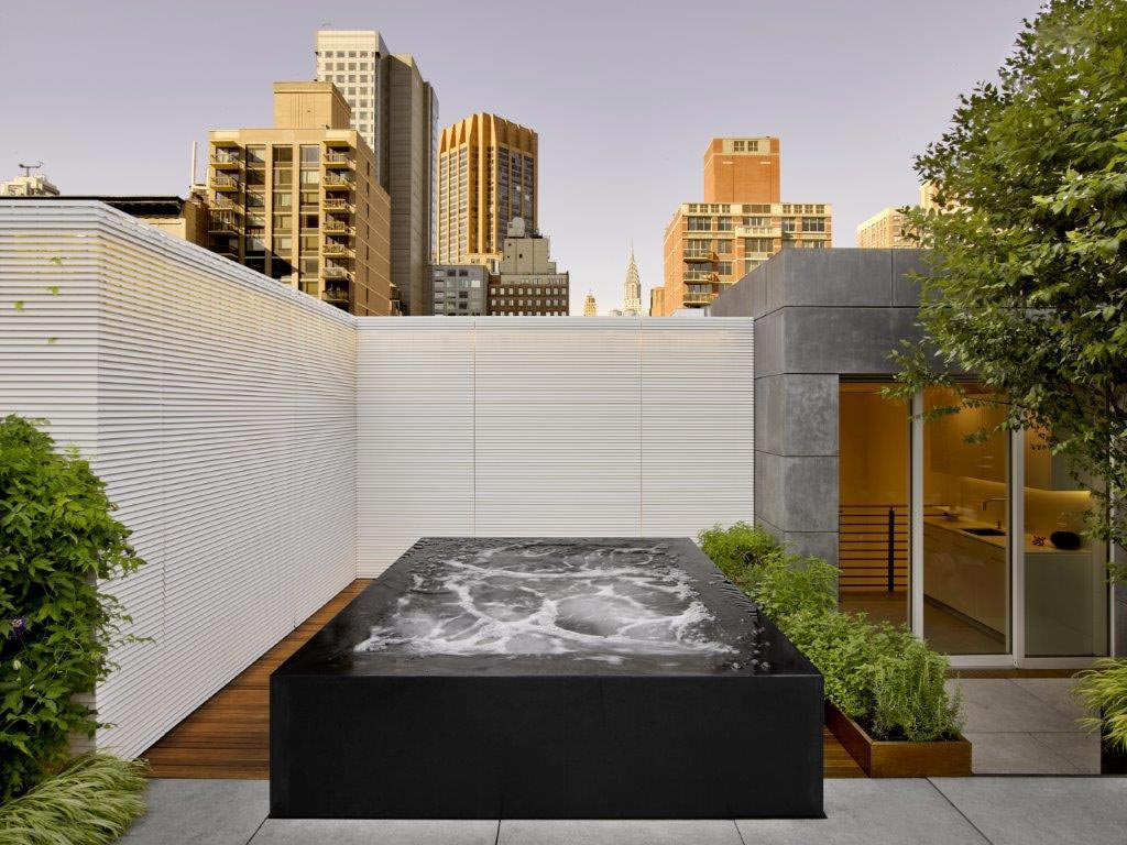 Stainless steel rooftop spa with four sided infinity edge and black overlay.  117